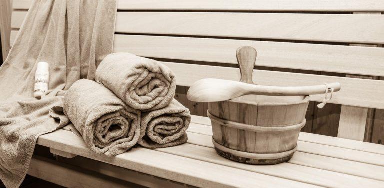 Innenraum einer Sauna mit Holvertäfelung, Kelle, Handtüchern und Eimer