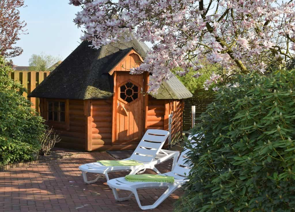 schöner Garten mit Gartensauna und zwei weißen Liegestühlen