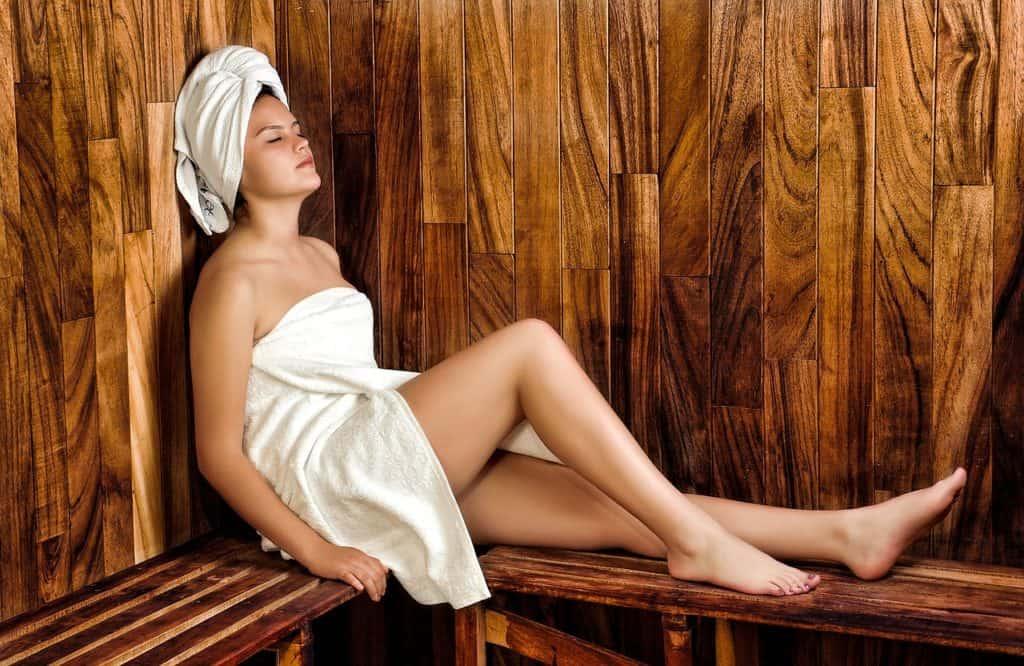 Frau mit weißem Handtuch in Sauna