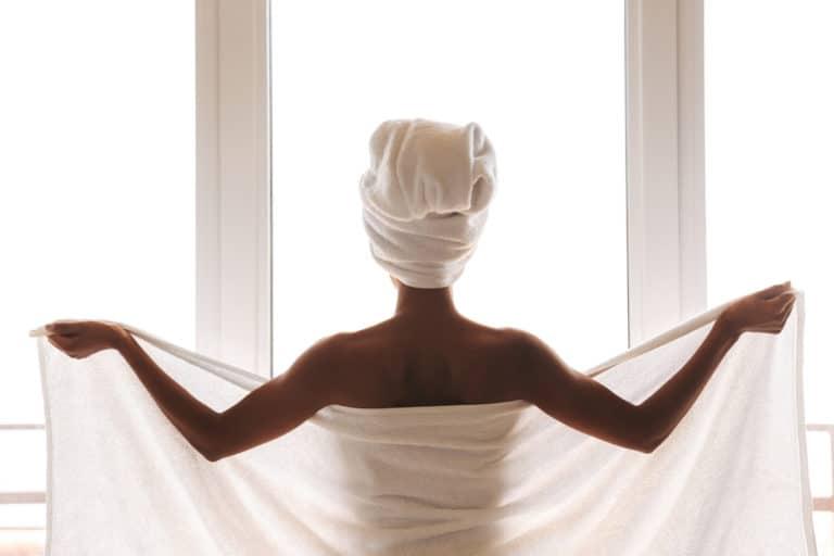 Frau steht mit geöffnetem weißen Saunahandtuch vor einer großen Fensterfront