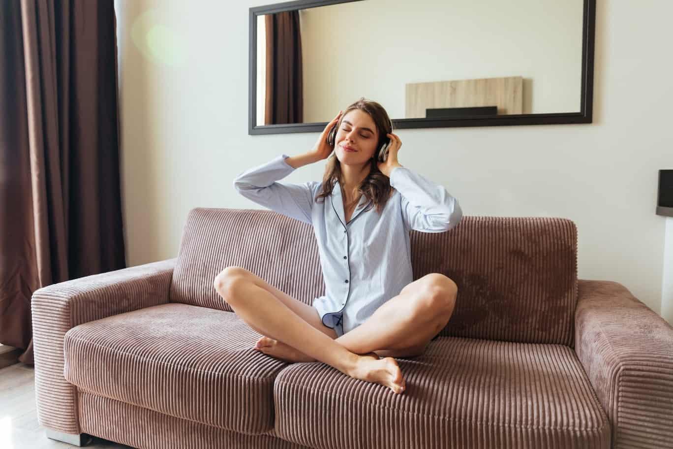 Sauna-Lautsprecher - Frau sitzt mit Kopfhörern und im Pyjama auf dem Sofa