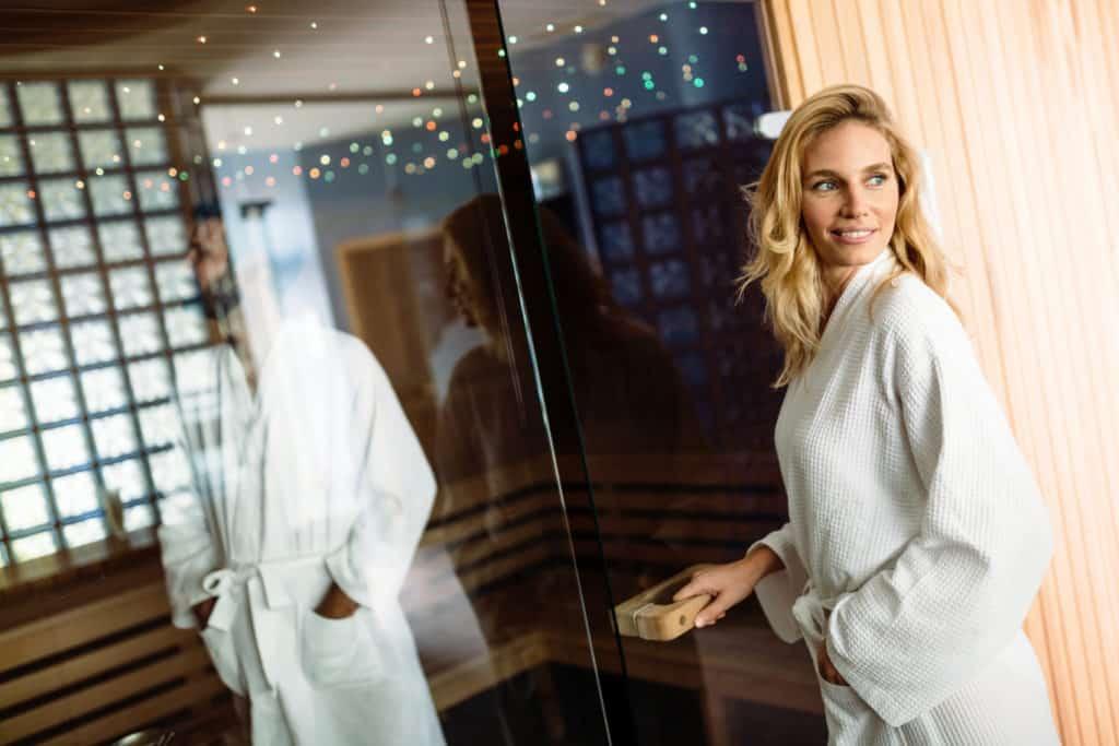 Frau im Bademantel öffnet Saunakabine mit Glas - dahinter Mann in Bademantel