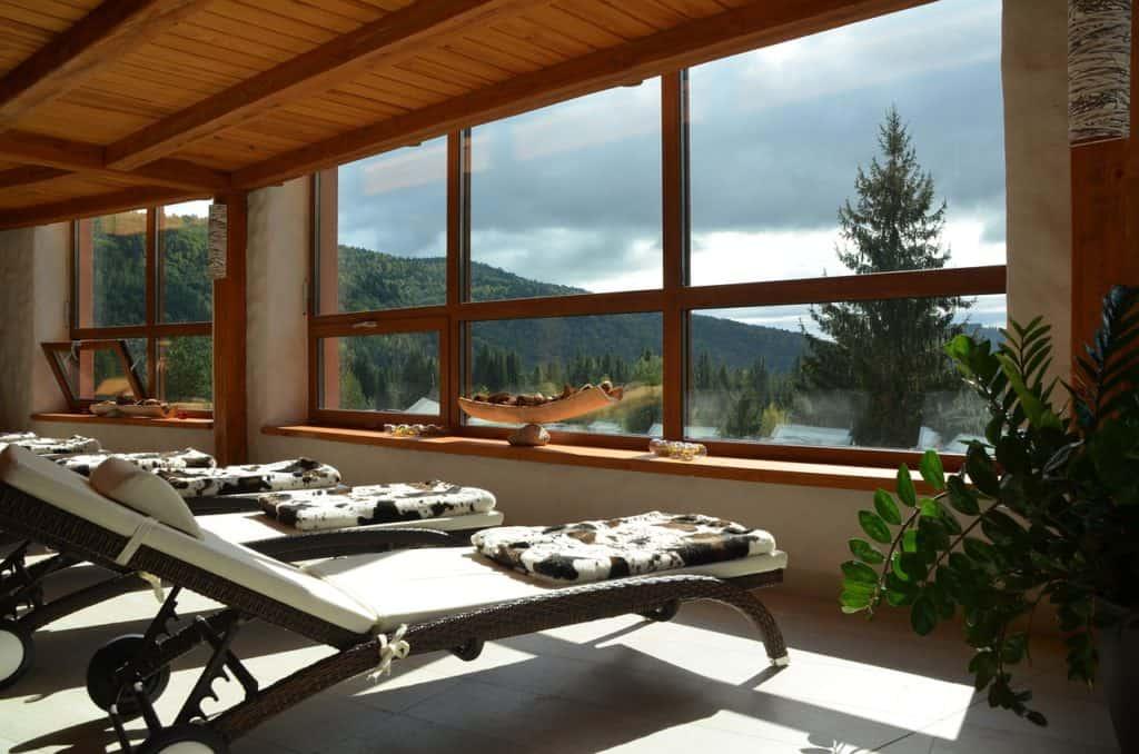 Saunaliege - Relaxliegen mit weißen Polstern im Spa mit Ausblick in den Bergen