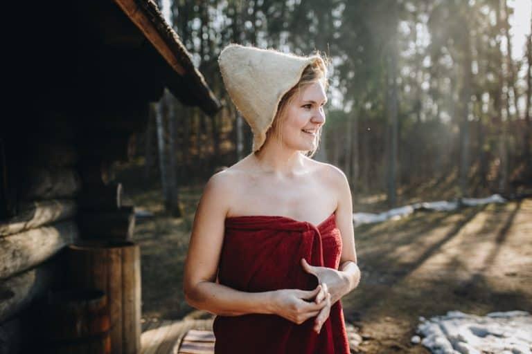 Frau mit Handtuch und Saunahut vor einer Gartensauna