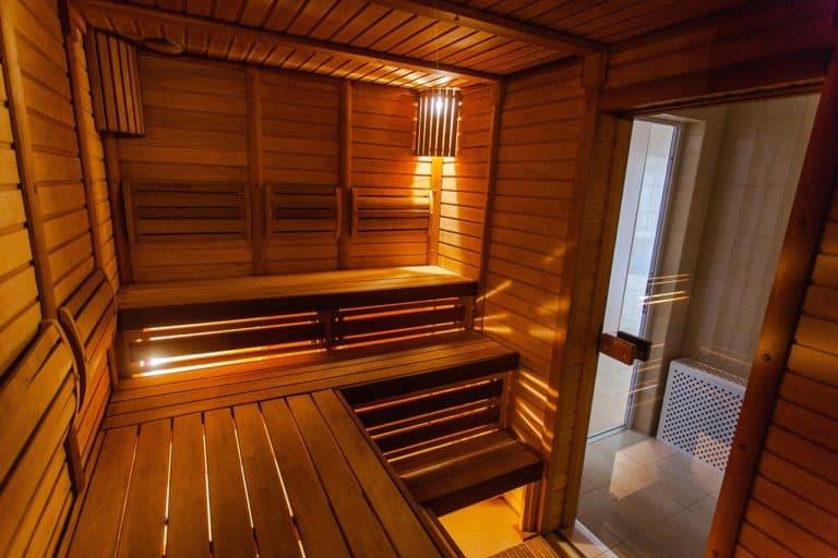 Saunahaus von innen mit Holzbänken und Glastür