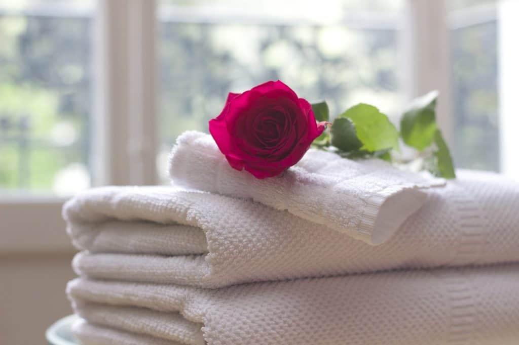 Stapel weißer Handtücher mit einer roten Rose darauf - im Hintergrund ein Fenster