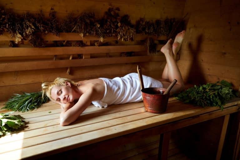 Frau liegt ohne Saunakissen oder Kopfstütze in Holzsauna
