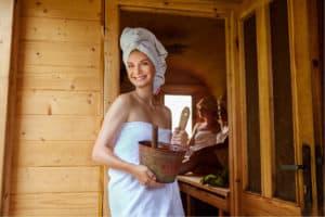 Frau in der Sauna - lächelnd mit Eimer und Kelle