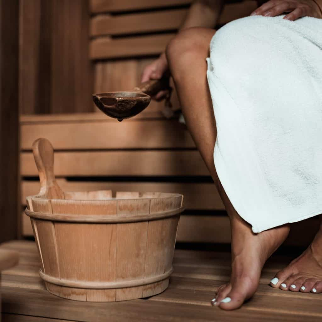 Frau mit Aufgusskelle in Ecksauna - Beine und Bank sichtbar